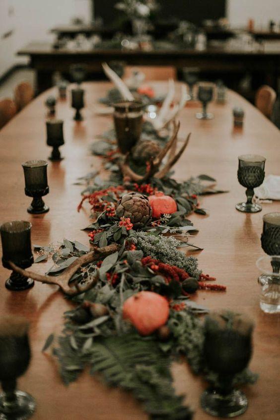 a fall wedding tablescape done with a greenery, red bloom adn berry runner, moss, artichokes, pomegranates and antlers is fantastic