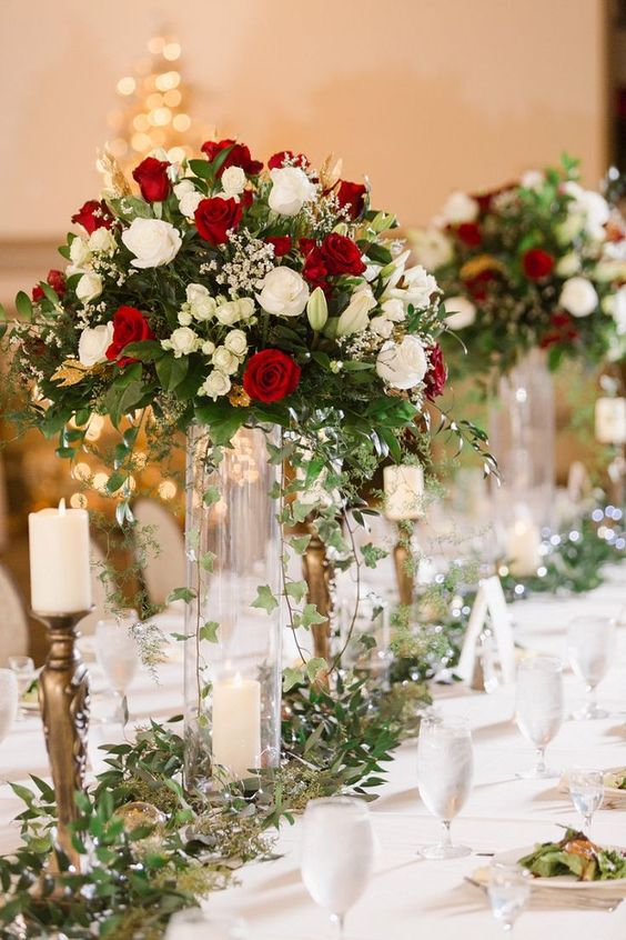 a festive Christmas wedding centerpiece of greenery, red and white blooms and a greenery runner and candles is chic and bold
