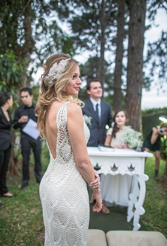 a fitting crochet wedding dress with thick straps and an open back plus a beautiful embellished headpiece for a lovely summer bridal look