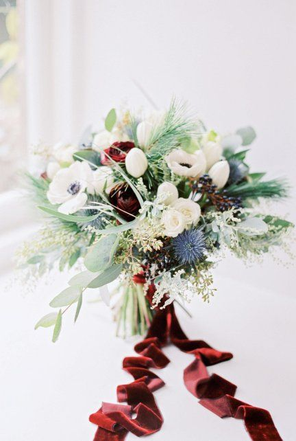 a frozen Christmas wedding bouquet of white and blue blooms, greenery and fir plus burgundy velvet ribbons