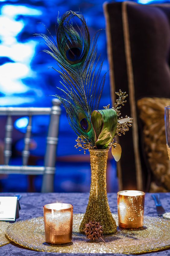 a gold glitter vase with leaves and peacock feathers make up a bold and glam centerpiece
