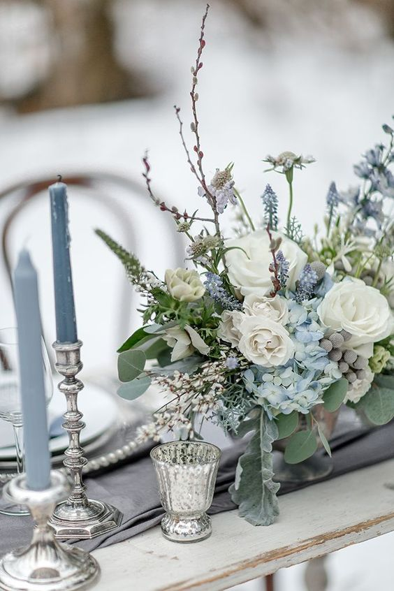a grey and ice blue winter wedding tablescape with a floral arrangement, mercury glass candleholders is very refined and chic
