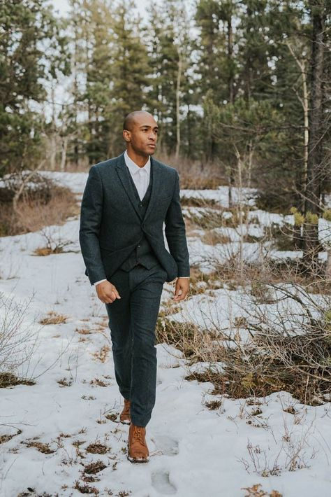 a grey tweed three piece suit, a white shirt and a tie plus brown boots for a winter wedding