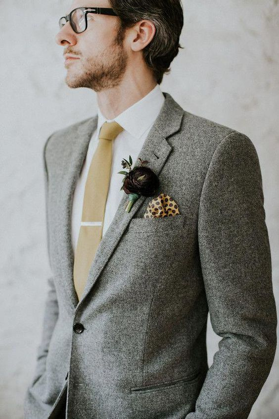 a grey twees suit, a white button down, a tan tie, a dark purple floral boutonniere for an elegant winter groom's look