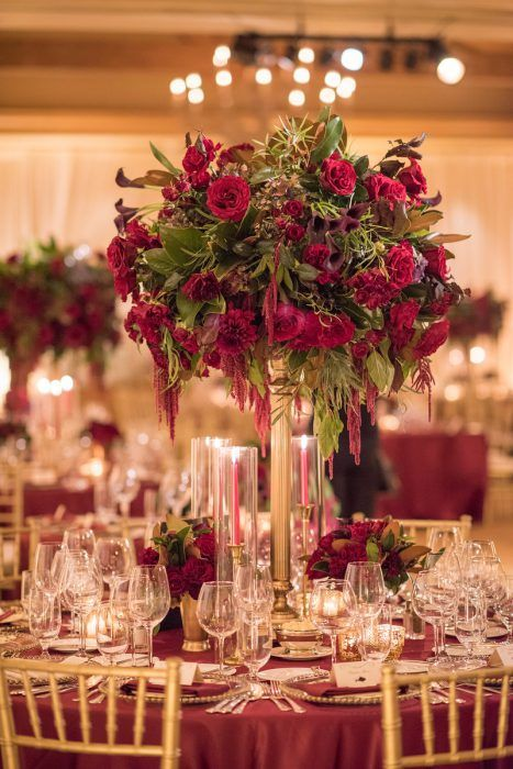a lush Christmas wedding centerpiece of a tall gold stand with burgundy and red blooms and greneery plus candles around