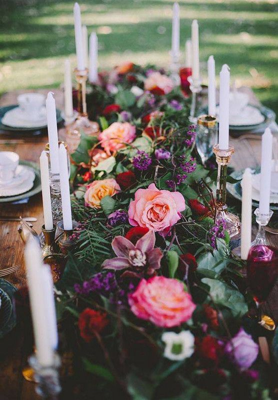 a lush and bold greenery and flower table garland done with purple, pink and mauve blooms looks very refined