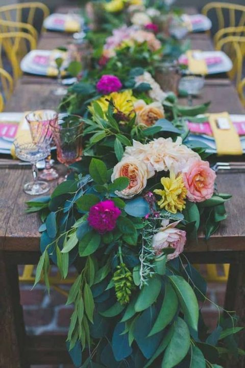 a lush and colorful greenery table garland with hot pink, blush and yellow blooms is great for a summer wedding