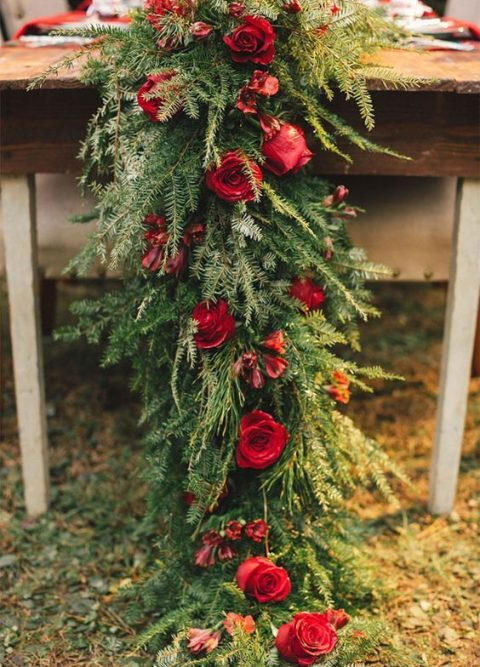 a lush evergreen table runner with red roses for a rustic holiday wedding