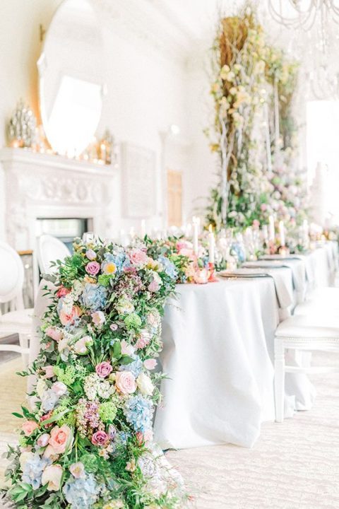 a lush floral table garland with greenery, lilac, pink, blue and yellow blooms going down to the floor