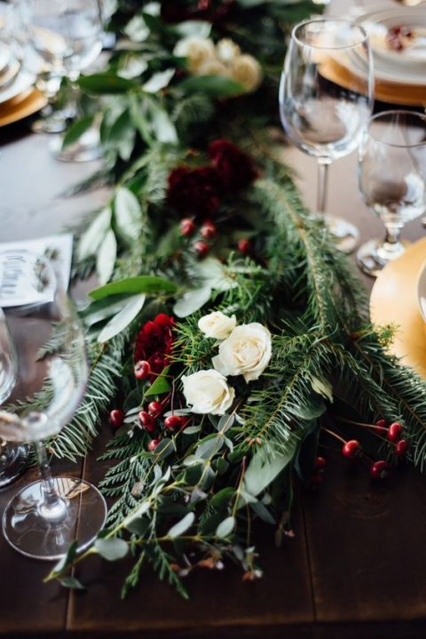 a lush greenery and evergreen table runner with white roses and berries for a Christmas wedding