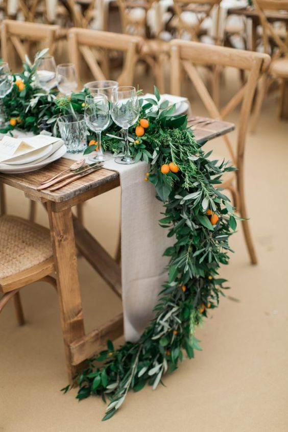 a lush greenery garland with some kumquats is a gorgeous idea for a modern or all-natural and rustic wedding
