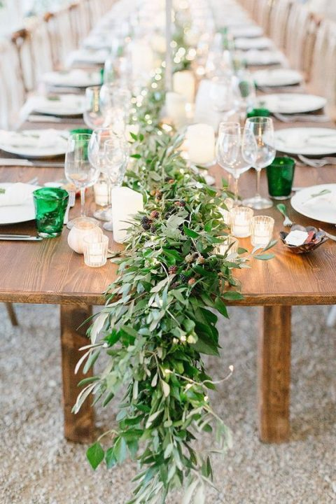 a lush greenery table garland with berries is a cool idea for a summer wedding