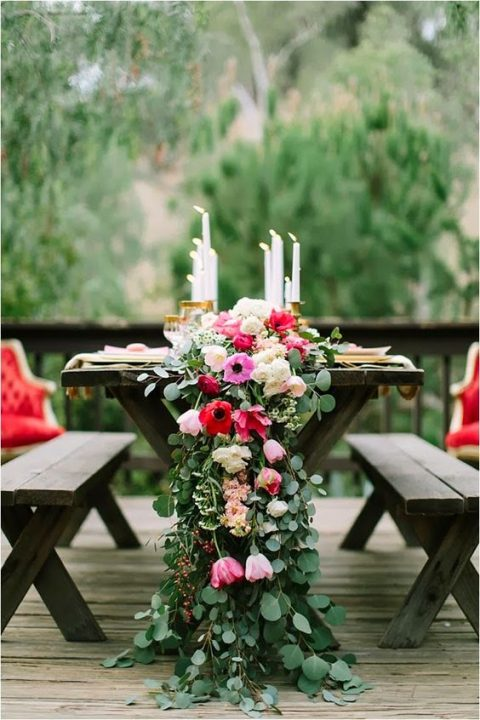 a lush greenery table garland with pink and red blooms and some candles