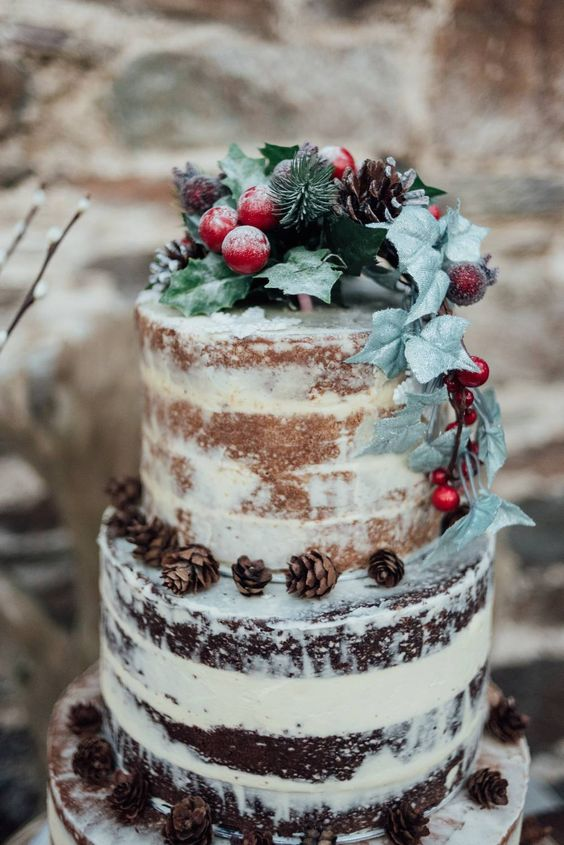 a naked Christmas wedding cake with pinecones, berries, apples and faux foliage is sepectacular
