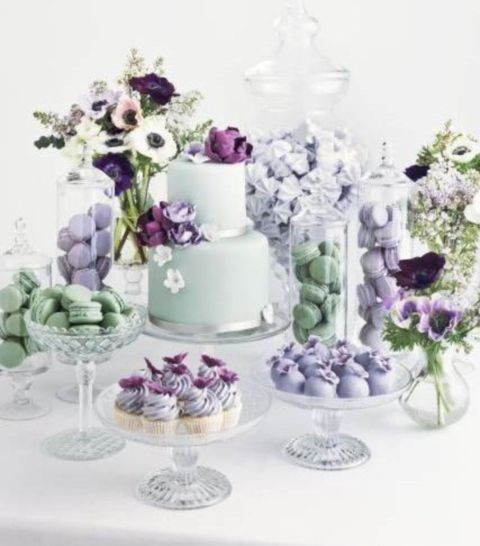 a mint and purple wedding sweets bar with purple and mint floral arrangements and all kinds of delicious desserts