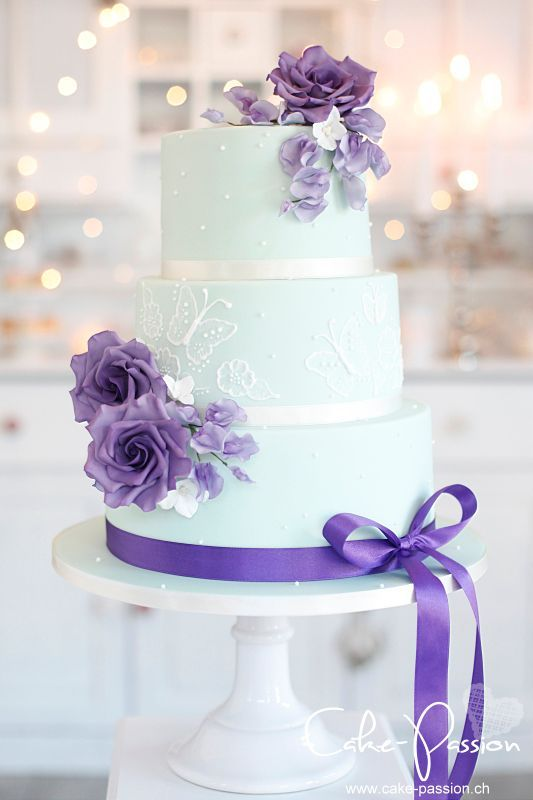 a mint wedding cake with white butterfly patterns, purple blooms and ribbon for a chic look