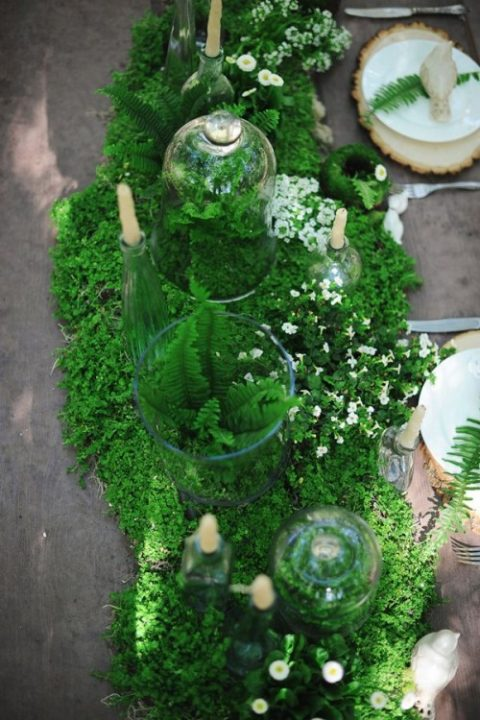 a moss and fern table runner with tiny white blooms and candles is a perfect fit for a woodland wedding