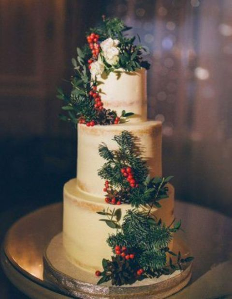 a naked wedding cake with berries, fit branches and pinecones plus some white blooms is classics with a rustic touch