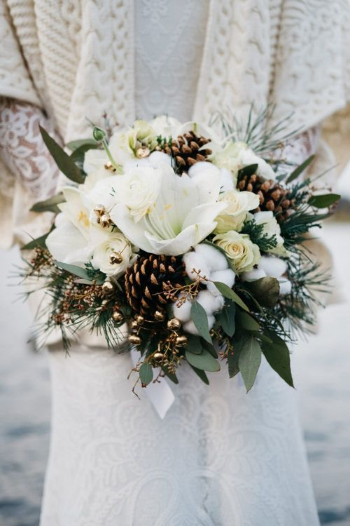 a neutral wedding bouquet of white blooms, pinecones, berries and greenery, gilded berries for Christmas