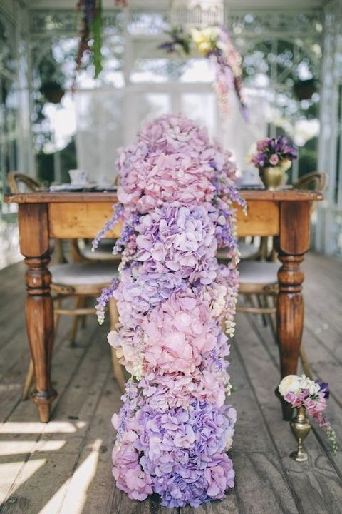 a pink and purple hydrangea floral table garland is a gorgeous floral statement at your reception