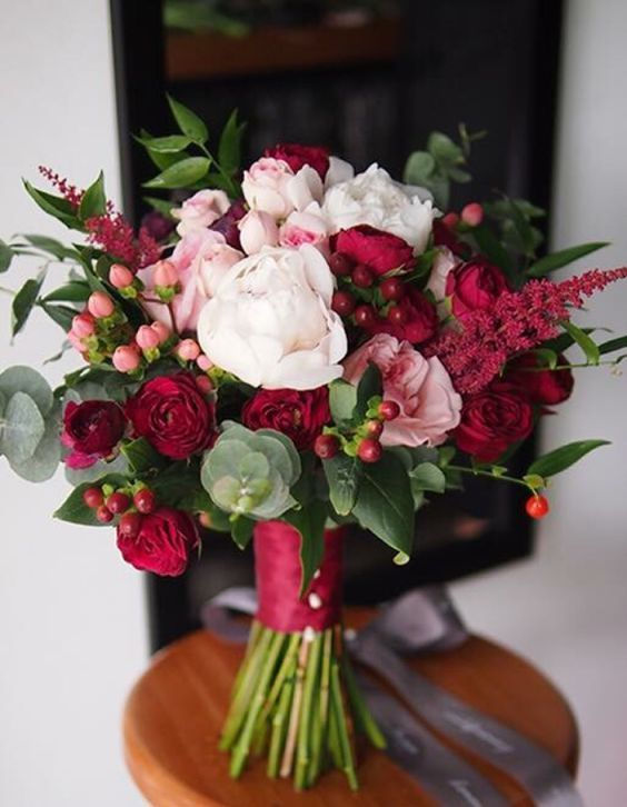 a pretty Christmas wedding bouquet of blush and burgundy blooms, berries and greenery plus a burgundy wrap