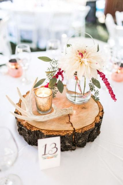 a pretty and bright wedding centerpiece of a wood slice, antlers, a candle and a neutral and pink bloom in a jar is easy to DIY