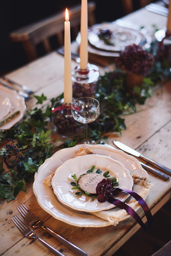 a refined Christmas table with greenery, dark blooms, privet berries, tall and thin candles and a burgundy bow