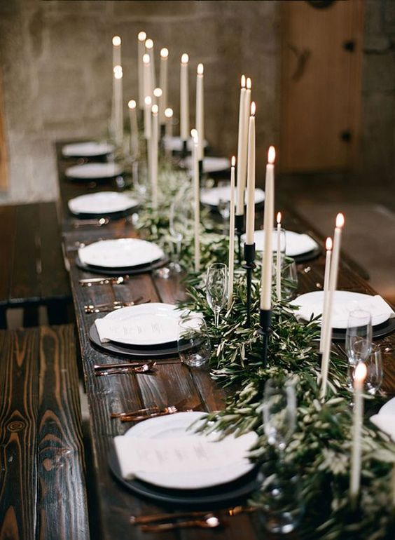 a refined Christmas tablescape with a greenery runner, tall and thin candles and black chargers plus white porcelain