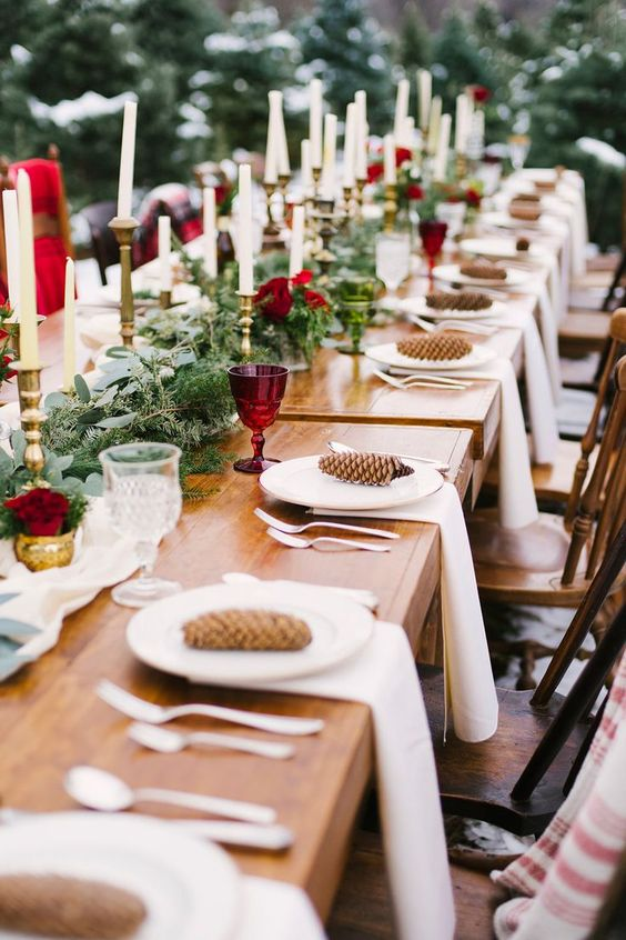a refined Christmas tablescape with an evergreen runner, burgundy blooms and glasses, tall and thin candles and pinecones
