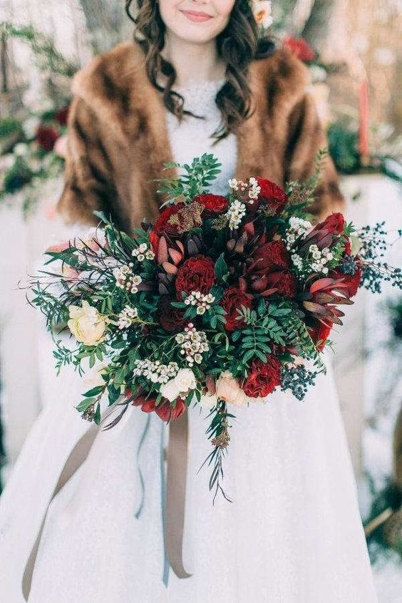 a refined Christmas wedding bouquet of burgundy and neutral blooms, greenery and berries plus neutral ribbons
