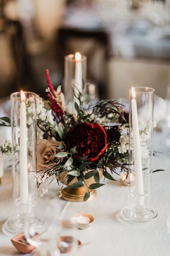 a refined Christmas wedding centerpiece of a gold bowl, greenery, burgundy and coffee roses and candles all around