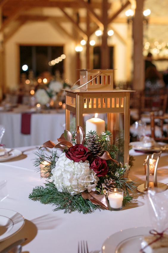 a refined Christmas wedding centerpiece of burgundy and white blooms, pinecones, greenery and a gold candle lantern is chic