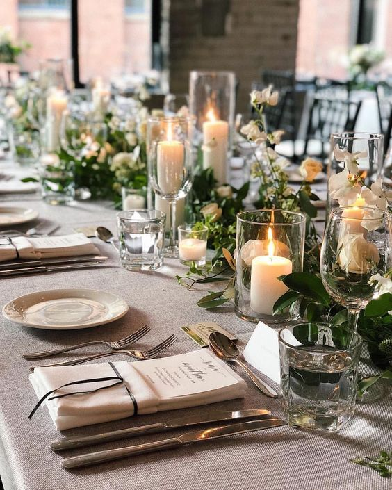 a refined Christmas wedding table setting with a greenery and white bloom runner, white candles, sivler cutlery and plates