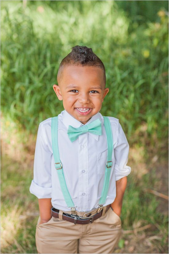 a ring bearer in khaki pants, mint suspenders and a bow tie looks lovely and very chic