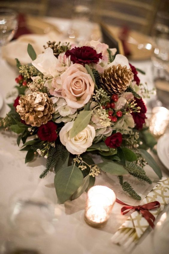 a romantic Christmas wedding centerpiece of burgundy, blush, white blooms, greenery, gilded pinecones and candles around