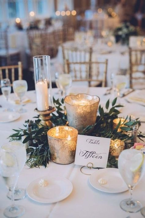 a romantic Christmas wedding centerpiece of greenery, mercury glass candleholders, a card and candles in glasses