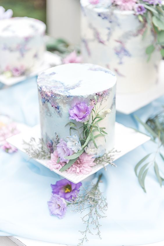 a romantic mint-colored floral wedding cake decorated wiht hand painting and purple and pink blooms