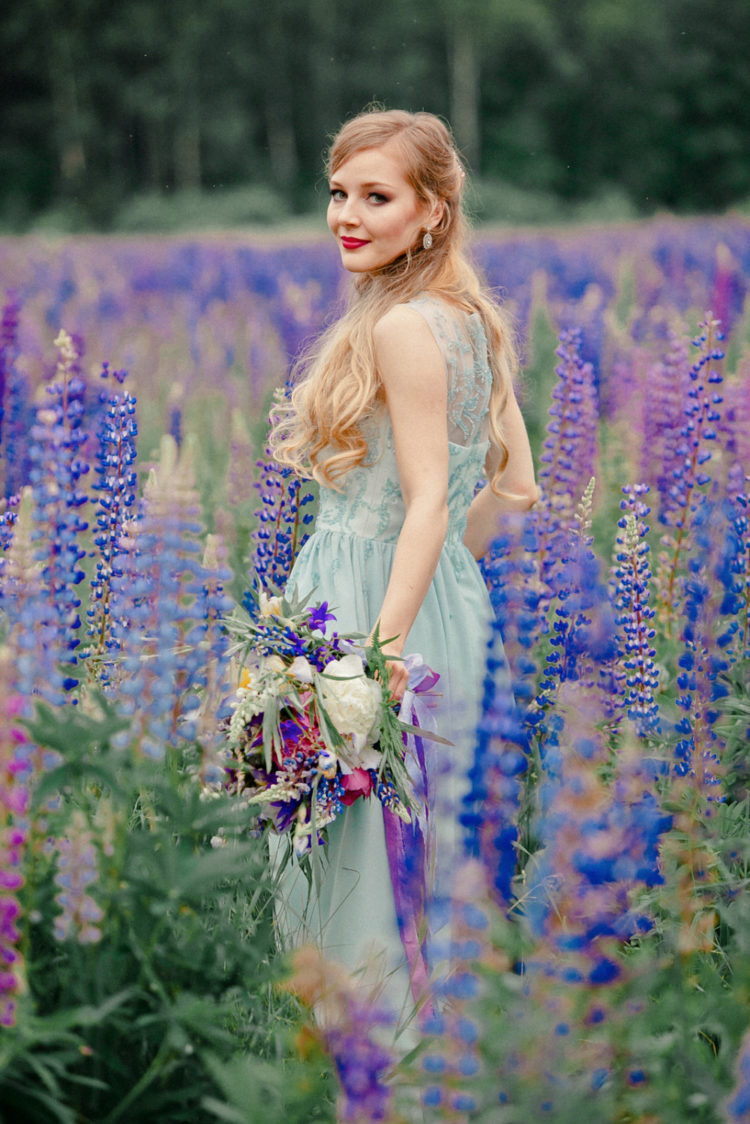 a romantic mint-colored wedding dress with embroidery and a lupine field for an ultimate bridal portrait