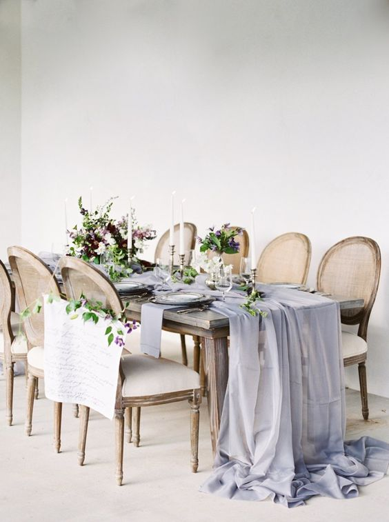 a romantic wedding tablescape with a lavender airy runner, purple blooms and greenery for a refined wedding
