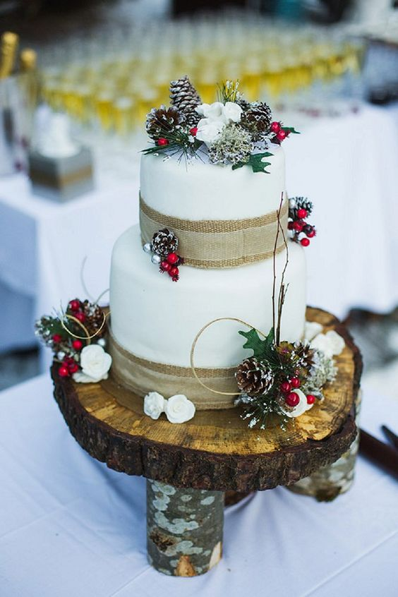 a rustic Christmas wedding cake with burlap ribbons, snowy pinecones, berries, leaves and some blooms is a pretty thing