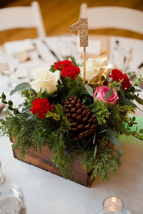 a rustic Christmas wedding centerpiece of a wooden box with greenery, red, pink and white blooms, pinecones and a glitter table number