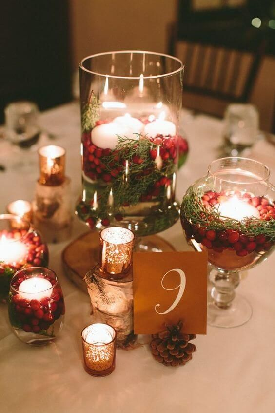 a rustic Christmas wedding centerpiece of glasses with cranberries, greenery and floating candles, wood slices and mercury glass candleholders