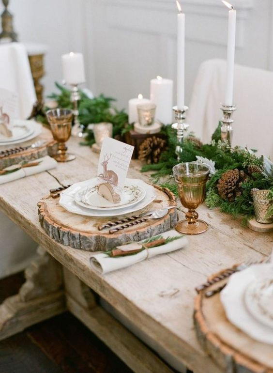 a rustic Christmas wedding tablescape with an evergreen and pinecone runner, various candles and wood slice placemats