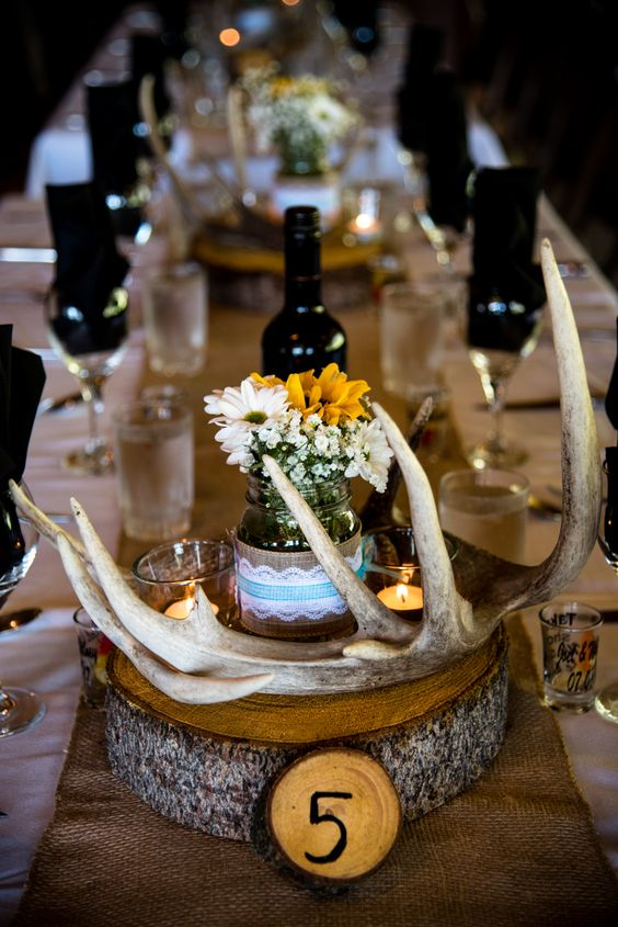 a rustic fall wedding centerpiece of a wood slice, antlers, simple blooms in a jar and candles is great for the fall