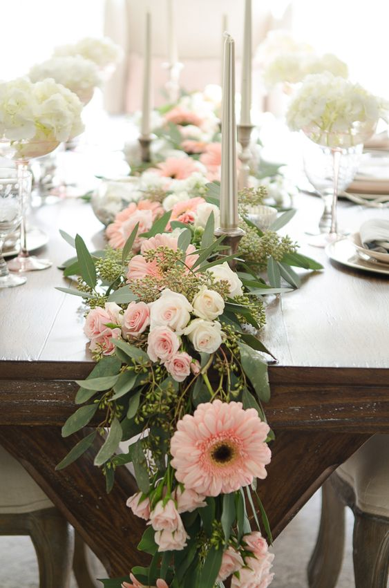 a seeded eucalyptus wedding table garland with white and blush blooms and silver candles is a chic idea