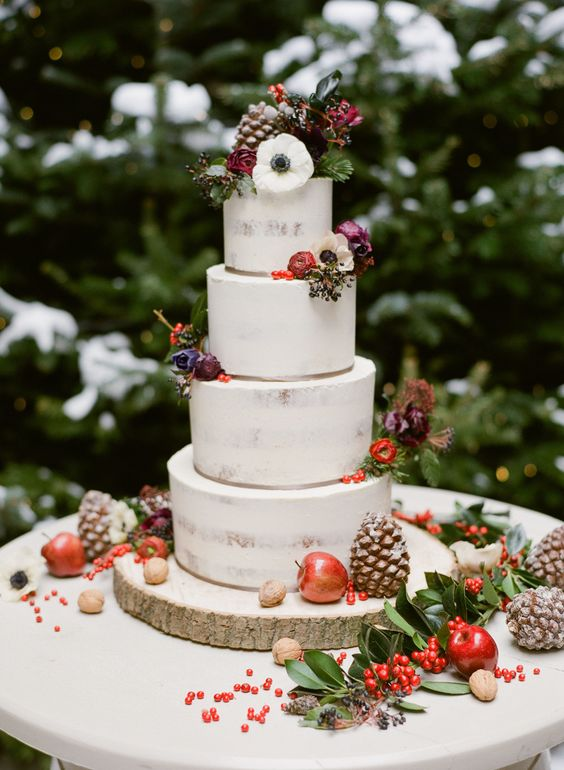 a semi naked Christmas wedding cake topped with dark blooms, berries, apples and gilded pinecones