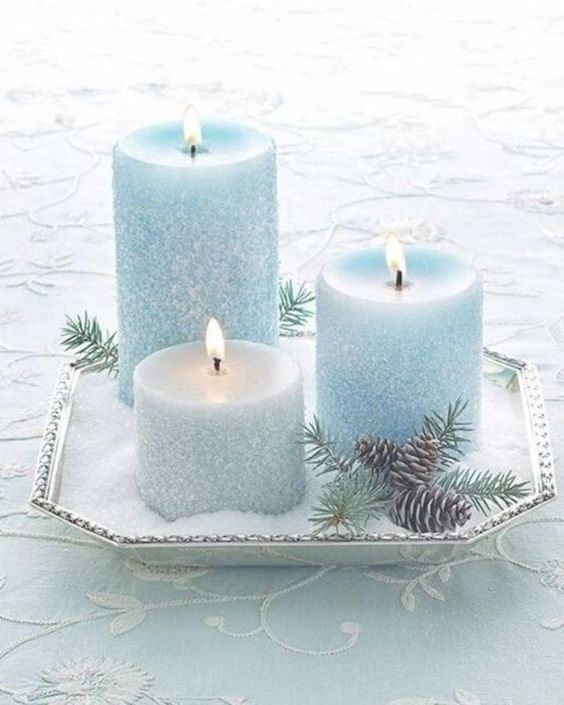 a silver tray with faux snow and silver and ice blue candles, pinecones and fir branches is a lovely centerpiece