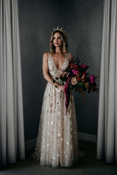 a sleeveless blush wedding dress with a plunging neckline, metallic stars and a crystal crown