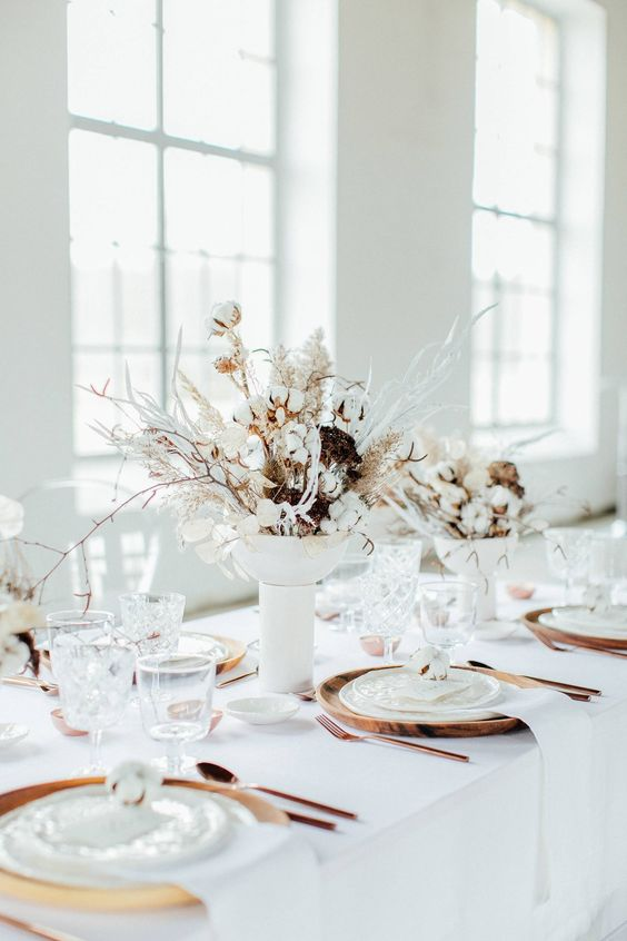 a snowy Christmas wedding centerpiece of a white vase with botton, dried herbs and white blooms and branches