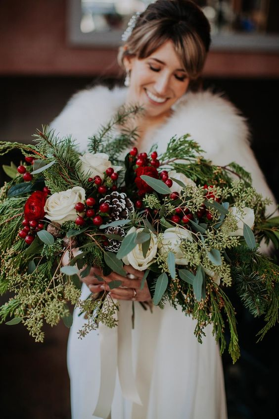 a spreading Christmas wedding bouquet of white blooms, berries, snowy pinecones, greenery and fir branches